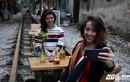 Khách nước ngoài thích thú uống cà phê trên đường ray tàu ở HN